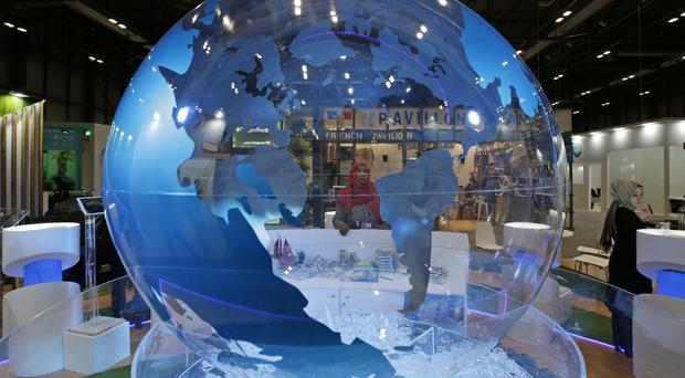 A woman looks at a World globe at the COP25 climate talks congress in Madrid (Paul White/AP)