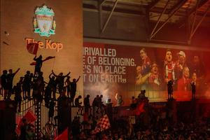 At the end of a storm: Liverpool's supporters begin to celebrate at Anfield after the club's 30 years wait for a league title was brought to a halt.