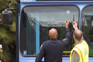 SANTA MONICA, CA - JUNE 07:  A police officer and a transit official look at a bullet hole, one of many, in a public transit bus in which two passengers were shot, after multiple shootings were reported at various locations including Santa Monica College June 7, 2013 in Santa Monica, California. According to reports, at least six people have died in the shootings.  (Photo by David McNew/Getty Images)