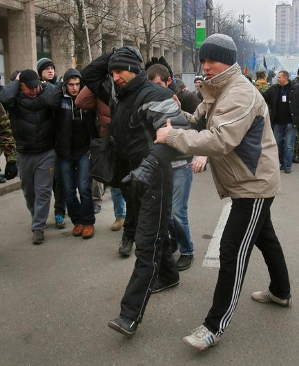 An opposition supporter, right, escorts people believed to be government-hired thugs away from an opposition camp in central Kiev, Ukraine, Tuesday, Jan. 21, 2014. About thirty young men believed to be hired by the government to instigate violence were detained by opposition activists last night. Opposition leader Vitali Klitschko accused the government of paying thugs to delegitimize the protests through violence. He said that the thugs, who were tasked with smashing windows and burning cars, were chased away by protesters. (AP Photo/Sergei Grits)