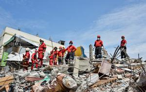 Peruvian rescuers pause their search for survivors during a tremor in Manta, in the Ecuadorean coastal province of Manabi, on April 18, 2016 two days after a 7.8-magnitude quake hit the country. Rescuers and desperate families clawed through the rubble Monday to pull out survivors of an earthquake that killed 350 people and destroyed towns in a tourist area of Ecuador. / AFP PHOTO / LUIS ACOSTALUIS ACOSTA/AFP/Getty Images