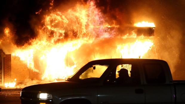 FERGUSON, MO - NOVEMBER 25:  A car drives by a burning building during a demonstration on November 25, 2014 in Ferguson, Missouri. Ferguson has been struggling to return to normal after Brown, an 18-year-old black man, was killed by Darren Wilson, a white Ferguson police officer, on August 9. His death has sparked months of sometimes violent protests in Ferguson. A grand jury today declined to indict officer Wilson.  (Photo by Justin Sullivan/Getty Images)