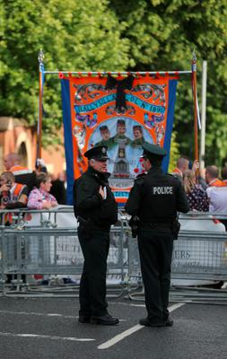 Police look on as Orange Order members march on Woodvale Road in Belfast as part of the annual Twelfth of July parades across Northern Ireland. PA