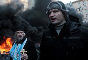 Opposition leader and former WBC heavyweight boxing champion Vitali Klitschko addresses protesters near the burning barricades between police and protesters in central Kiev, Ukraine, Thursday Jan. 23, 2014.   Klitschko dove behind the wall of black smoke engulfing much of downtown Kiev on Thursday, pleading with both police and protesters to uphold the peace until the ultimatum, demanding that Yanukovych dismiss the government, call early elections and scrap harsh anti-protest legislation that triggered the violence, expires Thursday evening. (AP Photo/Sergei Chuzavkov)