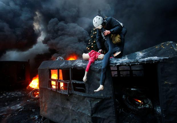 A protester breaks up a mannequin on the roof of the burned truck during clashes with police in central Kiev, Ukraine, Thursday Jan. 23, 2014. Thick black smoke from burning tires engulfed parts of downtown Kiev as an ultimatum issued by the opposition to the president to call early election or face street rage was set to expire with no sign of a compromise on Thursday. (AP Photo/Sergei Grits)