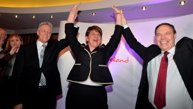 BELFAST, NORTHERN IRELAND - DECEMBER 17:  The new DUP leader Arlene Foster (C) is congratulated by outgoing leader Peter Robinson (L) and deputy leader Nigel Dodds (R) at the Park Avenue hotel after the Democratic Unionist Party electoral college meeting on December 17, 2015 in Belfast, Northern Ireland. Arlene Foster succeeds Peter Robinson and becomes the first female leader of the Democratic Unionist Party. No other nominations were put forward for the role of leader. Mrs Foster will also be appointed as the new Northern Ireland first minister in the coming weeks. The former Ulster Unionist Party member has enjoyed a rapid rise through the ranks of the DUP following her defection in 2004, twice standing in as temporary first minister for Peter Robinson in times of personal and political crisis. The DUP remain the largest political party within the provinces' Executive government.  (Photo by Charles McQuillan/Getty Images)