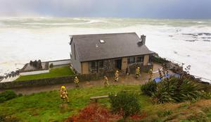 Fire fighters working to secure a house close to the cliff on Strand Road in Portstewart. Pic Kevin Scott / Belfast Telegraph
