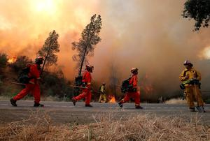 CLEARLAKE, CA - AUGUST 03:  Inmate firefighters march along highway 20 as they conduct a backfire operation to head off the Rocky Fire on August 3, 2015 near Clearlake, California. Nearly 3,000 firefighters are battling the Rocky Fire that has burned over 60,000 acres has forced the evacuation of 12,000 residents in Lake County. The fire is currently 12 percent contained and has destroyed at least 14 homes. 6,300 homes are threatened by the fast moving  blaze.  (Photo by Justin Sullivan/Getty Images)