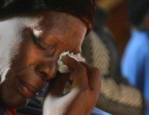 A worshipper weeps as she attends morning mass at the Regina Mundi Catholic Church in Soweto, South Africa, Sunday June 9, 2013. Churchgoers were urged to pray for former president Nelson Mandela who has been hospitalized with lung infection. The latest government report says that Mandela remains in a serious but stable condition. (AP Photo/Antione de Ras)