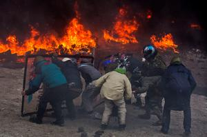 Protesters clash with police in central Kiev, Ukraine, Wednesday, Jan. 22, 2014. Two protesters whose bodies were found Wednesday near the site of clashes with police were shot with live ammunition, prosecutors said Wednesday, raising fears that their deaths  the first after two months of largely peaceful protests  could further fuel violence on the streets of the Ukrainian capital. (AP Photo/Evgeny Feldman)