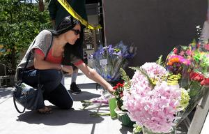 A woman leaves flowers at a makeshift memorial for victims of a balcony that collapsed in Berkeley (AP Photo/Jeff Chiu)