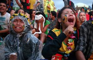 Brazil fans are devastated while watching the first half on Copacabana Beach during the 2014 FIFA World Cup semi-final match between Brazil and Germany on July 8, 2014 in Rio de Janeiro, Brazil. The winner advances to the final at the famed Maracana stadium.  (Photo by Mario Tama/Getty Images)