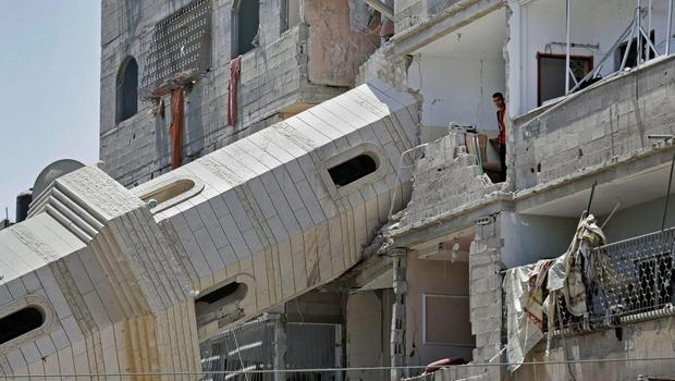 A Palestinian inspects damage to adjacent houses from a fallen minaret of the Al-Sousi mosque that was destroyed in an Israel strike, at the Shati refugee camp, in the northern Gaza Strip, Wednesday, July 30, 2014. (AP Photo/Lefteris Pitarakis)