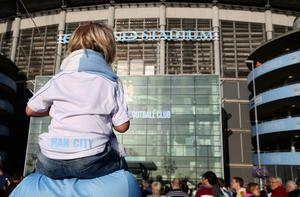 MANCHESTER, ENGLAND - AUGUST 19:  A young Manchester City fan sitting on shoulders looks at the Etihad Stadium main entrance prior to the Barclays Premier League match between Manchester City and Newcastle United at the Etihad Stadium on August 19, 2013 in Manchester, England.  (Photo by Clive Brunskill/Getty Images)