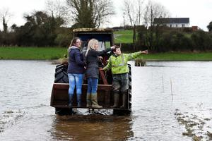 Agriculture and Rural Development Minister Michelle O'Neill with local schoolchildren, Kathleen McCaffrey (left) and Sean McCaffrey (right), as she views the impact of flooding on homes, roads and farmland at Innishroosk outside Lisnaskea. PA