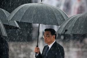 Chinese Premier Li Keqiang and Chinese Communist Party top leaders hold their umbrellas in the rain as they walk to the Monument to the People's Heroes during a ceremony marking the 64th anniversary of the founding of the People's Republic of China at Tiananmen Square on October 1, 2013 in Beijing, China. On October 1, 1949, Chinese leader Mao Zedong stood at the Tiananmen Rostrum to declare the founding of the People's Republic of China.  Photo by Feng Li