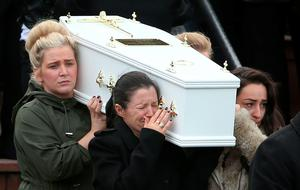 Louise James (front left) who lost her partner, two sons, sister and mother carries a coffin out of the Holy Family church, Ballymagroarty in Londonderry after the funeral of the five people who were killed when their car slid off a slipway in Co Donegal. PA