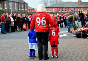 People pay their respects at the temporary Hillsborough memorial, ahead of a memorial service at Anfield in Liverpool, north west Engand on April 15, 2016, on the 27th anniversary of the Hillsborough Disaster. 96 Liverpool supporters died at the 1989 FA Cup semi-final between Liverpool and Nottingham Forest at the Hillsborough football ground in Sheffield, northern England. 2016 will be the final year a memorial service is held at Anfield. / AFP PHOTO / PAUL ELLISPAUL ELLIS/AFP/Getty Images