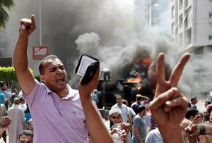 Supporters of Egypt's ousted President Mohammed Morsi chant slogans against Egyptian Defense Minister Gen. Abdel-Fattah el-Sissi during clashes with Egyptian security forces in Cairo's Mohandessin neighborhood, Egypt, Wednesday, Aug. 14, 2013. Egyptian security forces, backed by armored cars and bulldozers, swept in Wednesday to clear two sit-in camps of supporters of the country's ousted President Mohammed Morsi, showering protesters with tear gas as the sound of gunfire rang out at both sites. (AP Photo/Hassan Ammar)