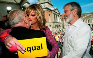 Drag queen and gay rights activist Rory O'Neill, known by his stage name as Panti Bliss kisses Senator David Norris (left) as Sinn Fein leader Gerry Adams looks on at the Central Count Centre in Dublin Castle, Dublin, as votes are continued to be counted in the referendum on same-sex marriage. PRESS ASSOCIATION Photo. Picture date: Saturday May 23, 2015. Ireland is set to enshrine the right to gay marriage in a historic world first. Key campaign groups fighting the rights reform conceded defeat, with results from around the country indicating a two to one majority of voters backing the constitutional change. See PA story IRISH GayMarriage. Photo credit should read: Brian Lawless/PA Wire