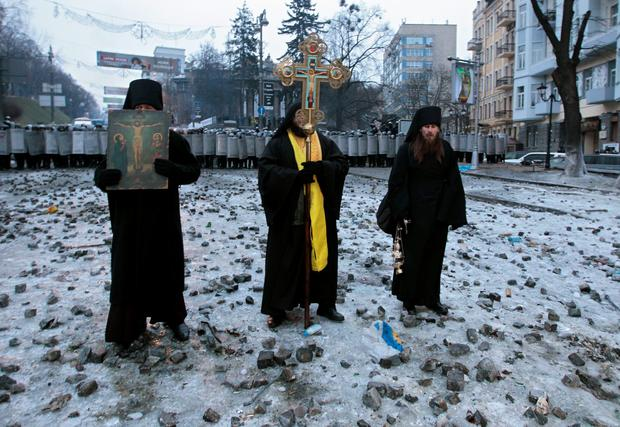 Orthodox priests pray as they stand between pro-European Union activists and police lines in central Kiev, Ukraine, Tuesday, Jan. 21, 2014. Anti-government protesters have held their ground through a night of violent street clashes in the Ukrainian capital, despite police moving in to dismantle barricades erected in a street leading to government offices. Police attempted to move in on the protest camp early Tuesday, but faced fierce resistance from demonstrators who tossed fire bombs and stones in their direction. (AP Photo/Sergei Chuzavkov)