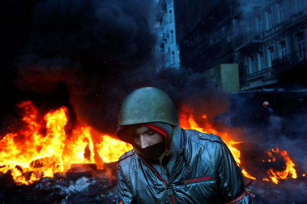 A protester walks pass burning tyres in central Kiev, Ukraine, Thursday Jan. 23, 2014. Thick black smoke from burning tires engulfed parts of downtown Kiev as an ultimatum issued by the opposition to the president to call early election or face street rage was set to expire with no sign of a compromise on Thursday. (AP Photo/Sergei Grits)