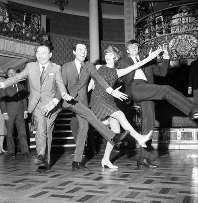 (Left to right) Joe Loss, Lionel Blair, Cilla Black, and Billy J Kramer demonstrate a new dance routine to accompany Joe Loss's new track Let's Kick in 1964. PA Wire.