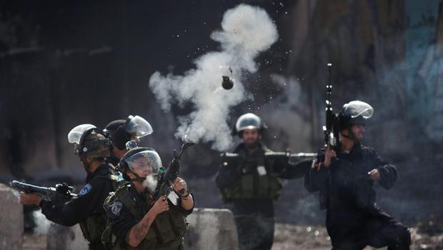 An Israeli border policeman fires a tear gas canister at Palestinian protesters during clashes following a protest against Israeli restrictions to Al-Aqsa Mosque in Jerusalem, at the Qalandia checkpoint near the West Bank city of Ramallah, Friday, Nov. 14, 2014. (AP Photo/Majdi Mohammed)