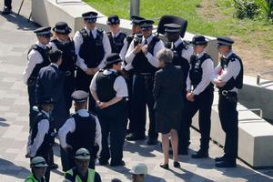 British Prime Minister Theresa May (C) speaks with police as she visits the remains of Grenfell Tower, a residential tower block in west London which was gutted by fire on June 14, 2017. Firefighters searched for bodies today in a London tower block gutted by a blaze that has already left 12 dead, as questions grew over whether a recent refurbishment contributed to the fire. / AFP PHOTO / Tolga AKMENTOLGA AKMEN/AFP/Getty Images