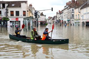 People paddle in a craft in a flooded street on June 1, 2016 in Nemours. Torrential downpours have lashed parts of northern Europe in recent days, leaving four dead in Germany, breaching the banks of the Seine in Paris and flooding rural roads and villages.KENZO TRIBOUILLARD/AFP/Getty Images