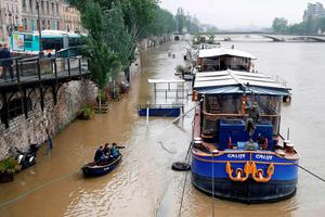 People access a tourist crusing barge on Quai de Conti using a small boat, after the banks of the river Seine became flooded following heavy rainfalls on June 1, 2016 in Paris.   Torrential downpours have lashed parts of northern Europe in recent days, leaving four dead in Germany, breaching the banks of the Seine in Paris and flooding rural roads and villages. / AFP PHOTO / FRANCOIS GUILLOTFRANCOIS GUILLOT/AFP/Getty Images