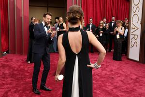 Jason Sudeikis, left, takes a cell phone photo of Olivia Wilde as they arrive at the Oscars on Sunday, March 2, 2014, at the Dolby Theatre in Los Angeles.  (Photo by Matt Sayles/Invision/AP)