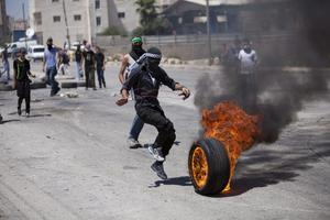 A masked Palestinian kicks a burning tire during clashes following a protest against thewar oin the Gaza Strip, outside Ofer, an Israeli military prison near the West Bank city of Ramallah, Friday, Aug. 1, 2014. (AP Photo/Majdi Mohammed)