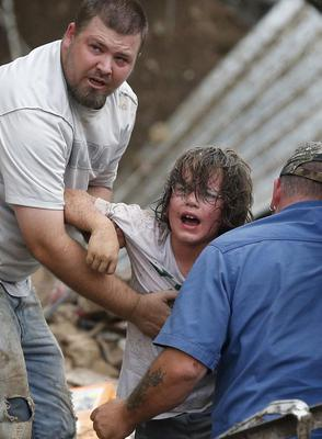 A child calls to his father after being pulled from the rubble of the Tower Plaza Elementary School following a tornado in Moore, Okla., Monday, May 20, 2013. A tornado as much as a mile (1.6 kilometers) wide with winds up to 200 mph (320 kph) roared through the Oklahoma City suburbs Monday, flattening entire neighborhoods, setting buildings on fire and landing a direct blow on the elementary school. (AP Photo/Sue Ogrocki)