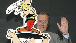 French author and illustrator Albert Uderzo waves from behind a cardboard cutout showing his comic heroes Asterix and Obelix (Joerg Sarbach/AP)
