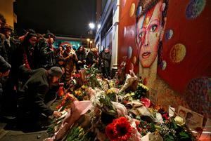 LONDON, ENGLAND - JANUARY 11: A woman leaves flowers beneath a mural of David Bowie in Brixton on January 11, 2016 in London, England. British music and fashion icon David Bowie died earlier today at the age of 69 after a battle with cancer. (Photo by Carl Court/Getty Images)