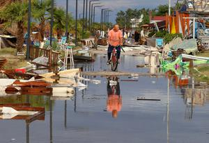 A man rides a bicycle among debris after a storm at Nea Plagia village in Halkidiki region, northern Greece. Credit: Giannis Moisiadis/InTime News via AP