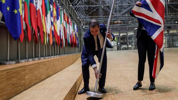 EU Council staff members remove the UK flag from the European Council building in Brussels