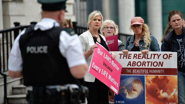 BELFAST, NORTHERN IRELAND - MAY 31: Bernie Smyth (L) of Precious Lives holds a counter pro life protest as abortion rights campaign group ROSA, Reproductive Rights Against Oppression, Sexism and Austerity distribute abortion pills from a touring bus on May 31, 2018 in Belfast, Northern Ireland. Flouting Northern Irish governmental laws which forbid the use of abortion pills the group are also protesting outside offices belonging to the main political parties in the province. Women in Northern Ireland have been prosecuted for buying abortion pills over the internet and it is illegal for a woman to have an abortion unless in special circumstances unlike the rest of the United Kingdom. The Republic of Ireland voted in favour of pro-choice last week in a referendum. (Photo by Charles McQuillan/Getty Images)