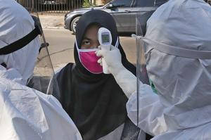 Health workers take the body temperature reading of a woman during a mass test in Tangerang, Indonesia (Tatan Syuflana/AP)