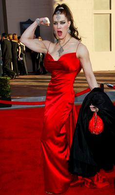 FILE - In this Nov. 16, 2003 dil photo, Joanie Laurer, former pro wrestler known as Chyna, flexes her bicep as she arrives at the 31st annual American Music Awards, in Los Angeles. Chyna, the WWE star who became one of the best known and most popular female professional wrestlers in history in the late 1990s, has died at age 45. Los Angeles County coroners Lt. Larry Dietz says Chyna, whose real name is Joan Marie Laurer, was found dead in Redondo Beach on Wednesday, April 20, 2016. (AP Photo/Kevork Djansezian)