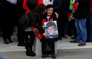 A woman holds an image of a victims of the 1989 Hillsborough disaster, as she reacts following the conclusion of the inquest into the disaster, at the coroner's court in Warrington, north-west England on April 26, 2016. The 96 Liverpool fans who died in Britain's 1989 Hillsborough football stadium disaster were unlawfully killed, a jury found Tuesday following the longest-running inquest in English legal history. After hearing more than two years of evidence, the jury also concluded that the behaviour of Liverpool supporters on the day did not cause or contribute to Britain's worst sports stadium tragedy.  / AFP PHOTO / GEOFF CADDICKGEOFF CADDICK/AFP/Getty Images