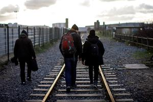 CALAIS, FRANCE - FEBRUARY 28:  Migrants walk along a railway line near the 'jungle' camp on February 28, 2016 in Calais, France. The French authorities have begun dismantling part of the jungle encampment and relocating migrants to purpose-built accommodation nearby.  (Photo by Carl Court/Getty Images)