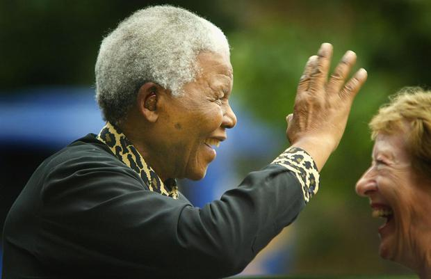 LONDON - JULY 10:  International humanitarian and former South African president, Nelson Mandela (L) waves to the crowd as he arrives at the Queen Elizabeth II Conference Hall July 10, 2003 in London, England.  Mandela was to give a lecture in aid of the British Red Cross, praising their work and highlighting HIV and AIDS issues. (Photo by Scott Barbour/Getty Images)