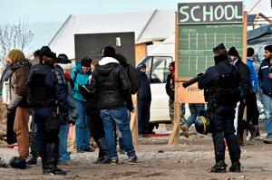 "Anti-riot policemen stand next to a school sign and gathered people as agents dismantle shelters on February 29, 2016 in the ""jungle"" migrants and refugees camp in Calais, northern France.  A French court on February 25 gave the green light to plans to evacuate hundreds of migrants from the southern half of the sprawling camp in the port town, with many wanting to stay near the entrance to the Channel Tunnel, the gateway to their ultimate goal of Britain. AFP PHOTO / PHILIPPE HUGUENPHILIPPE HUGUEN/AFP/Getty Images"