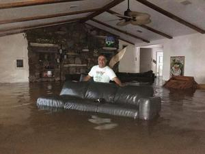 This Sunday, Aug. 27, 2017, photo provided by Ramit Plushnick-Masti, shows her husband, Rafi, standing in waist-high water inside their flooded home in Houston's Meyerland neighborhood that was caused by Tropical Storm Harvey. Plushnick-Masti and her family intended to ride out the storm in their Houston home, but their plan changed when the floodwaters rose over the weekend. (Ramit Plushnick-Masti via AP)