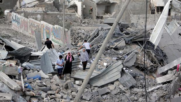 Palestinians walk by the rubble of houses destroyed by Israeli strikes, as they return the area during a 12-hour cease-fire in Beit Hanoun, northern Gaza Strip, Saturday, July 26, 2014.  (AP Photo/Lefteris Pitarakis)