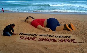 Indian artist Sudarsan Pattnaik works on a sand sculpture depicting drowned Syrian boy Aylan Kurdi at Puri beach, some 65 kilometers away from Bhubaneswar, on September 4, 2015. Charities helping refugees saw a surge in donations on September 4 across Europe as people shocked by the heart-rending images of a drowned Syrian boy on a Turkish beach dug deep to help out. The photos of the lifeless body of three-year-old Aylan Kurdi, lying on a beach in Bodrum, Turkey, have triggered a wave of emotion across the continent, despite deep divisions among European governments on how to deal with the crisis. AFP/Getty Images