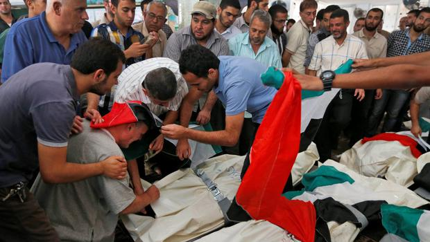 Palestinians try to comfort Hassan al-Halaq, bottom left, weeping over the body of his wife Souad, 62, during a funeral for five members of the family, including also his daughter-in-law Samar, 29, and his grandsons, Kena, 5, and Sadji, killed  Sunday by an Israeli strike at their house in Gaza City, Monday, July 21, 2014 (AP Photo/Lefteris Pitarakis)