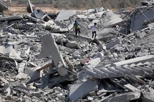 Palestinians inspect the damage of their destroyed houses following Israeli strikes in the village of Khuzaa, southern Gaza Strip, close to the Israeli border, Friday, Aug. 1, 2014.  (AP Photo/Khalil Hamra)